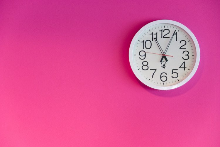 white clock on pink wall