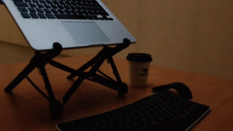 Roost laptop stand on desk with keyboard and mouse close up